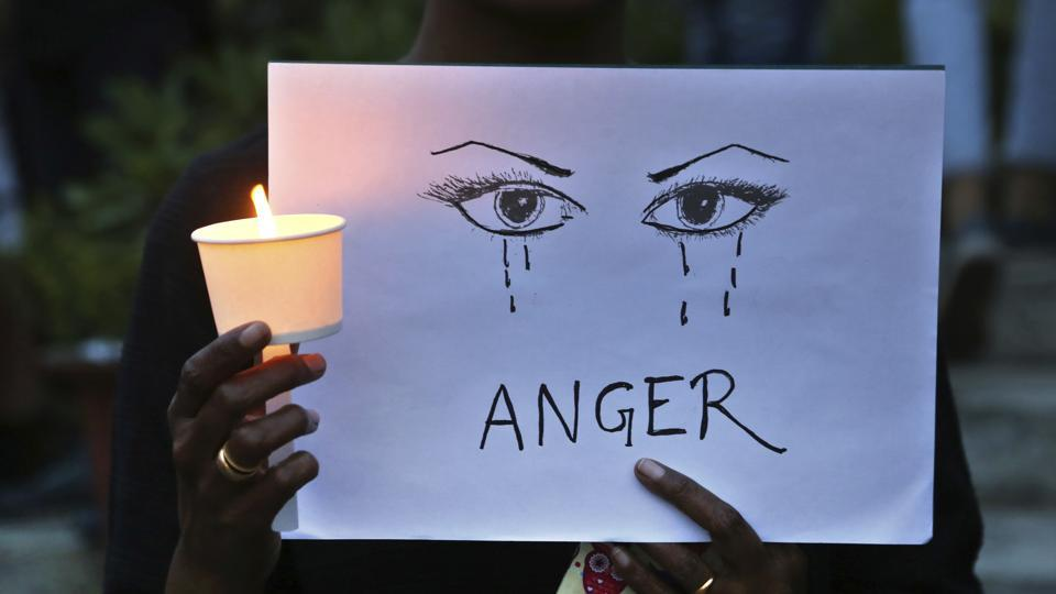 Awoman holds a candle and placard seeking an end to sexual violence against women and children. Alawyer was held for allegedly assaulting a minor girl on a train in Tamil Nadu.