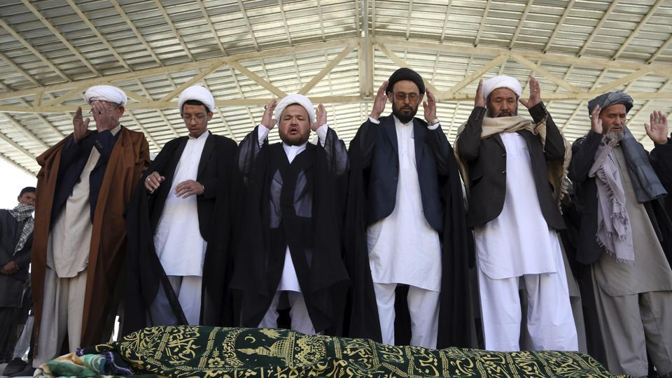 Afghan people offer funeral prayers behind the body of a civilian killed in Sunday's deadly suicide attack at a voter registration center, in Kabul, Afghanistan, on Monday.