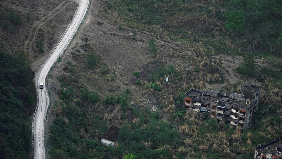 A vehicle drives past apartment blocks destroyed in a landslide caused by the 2008 earthquake, at the foot of a mountain. The 7.9 magnitude quake which hit on May 12, 2008 was most devastating around its epicentre in Beichuan. Many of the houses that collapsed remain buried under the earth and are covered by overgrown bushes and weeds. (Jason Lee / REUTERS)