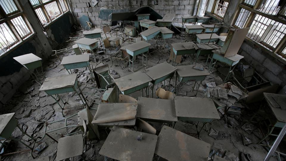 Desks stand in the classroom of Beichuan Vocational Education Centre. Damaged school classrooms remain a mess, with books on the desks turning black with rot. Signs in Chinese, English, Japanese, Korean and French urge visitors to be careful where they tread to let the dead rest in peace. (Jason Lee / REUTERS)