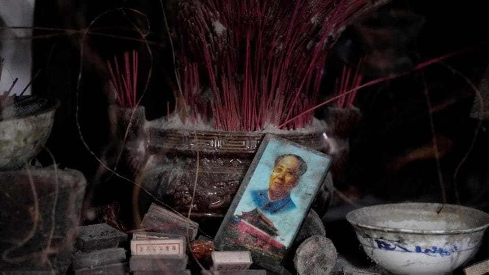 A card featuring the late Chinese Chairman Mao Zedong and Tiananmen Gate is seen next to a shrine in tan old destroyed home. Last August, a 7.0-magnitude quake in a mountainous part of Sichuan popular with tourists killed 20 and injured around 500. (Jason Lee / REUTERS)