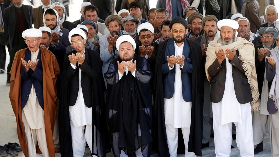 People perform prayers for one of the victims of yesterday's suicide attack before a burial ceremony in Kabul, Afghanistan April 23, 2018.