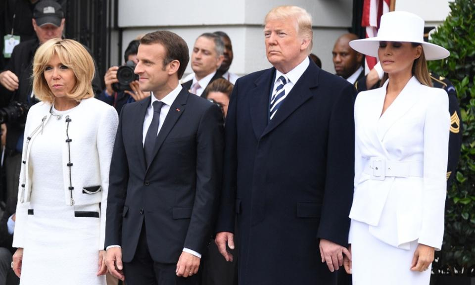 Melania, who donned a white outfit and a brimming white hat, stood next to her husband rigidly as he appeared to make a subtle effort to hold her hand.