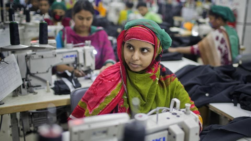 "Khadiza Begum, 23, who was trapped for hours after the Rana Plaza collapse was so shaken by the experience she didn't work for two years. Eventually, with her family desperately needing money, she got a job at Snowtex. ""It's very different here,"" she said, sitting in front of a sewing machine. ""This building is good and strong."" (A.M. Ahad / AP)"
