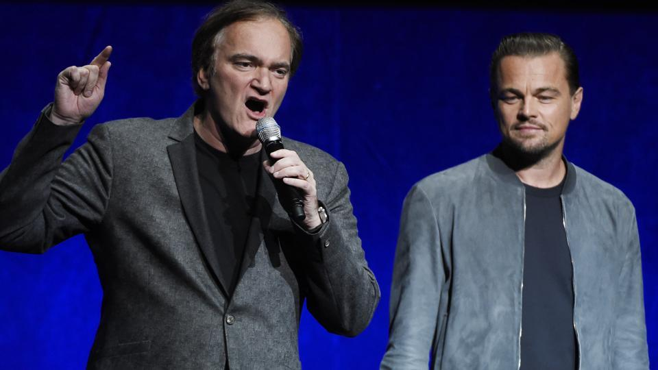 Quentin Tarantino, left, writer/director of the upcoming film Once Upon a Time in Hollywood, discusses the project as cast member Leonardo DiCaprio looks on during the Sony Pictures Entertainment presentation at CinemaCon 2018.