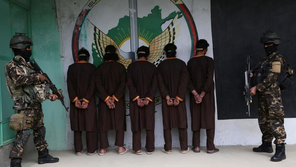 Afghan security forces stand next to Taliban militants as they are to the media in Ghazni province on April 14, 2018. Afghan security forces arrested five Taliban militants during an operation in Ghazni province.