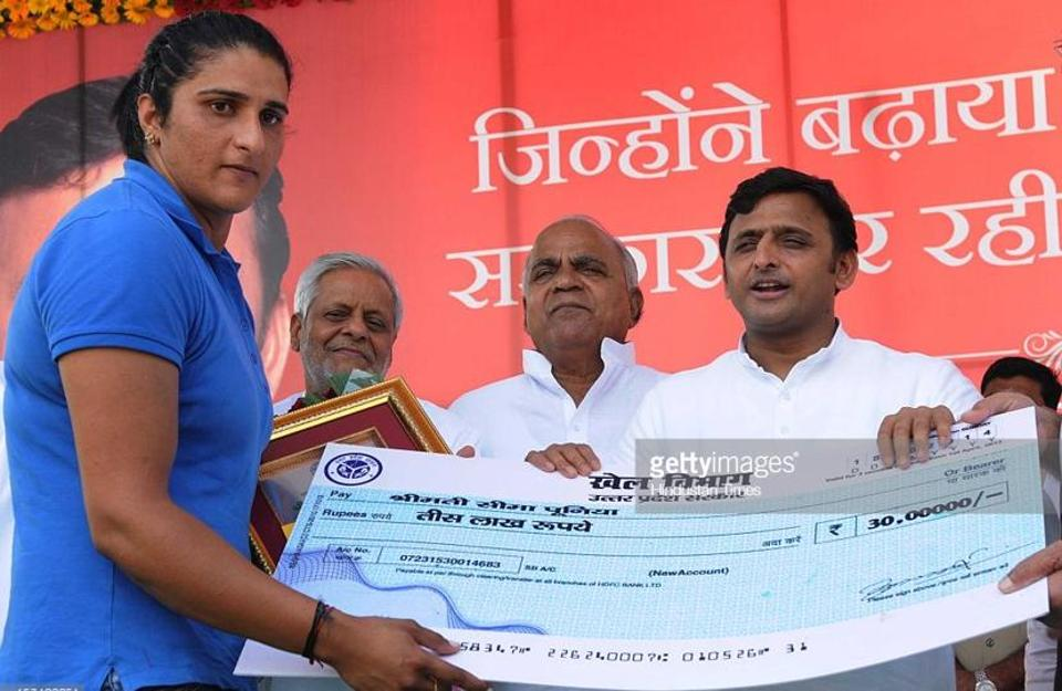 A file photo showing Seema Punia collecting a cheque from SP chief Akhilesh Yadav on winning a silver medal at the 2014 Glasgow Commonwealth Games.