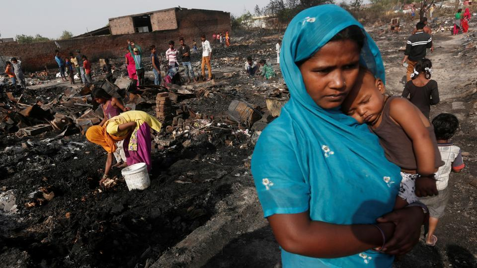 A woman and her daughter (L) rummage through debris for belongings after a fire broke out in a slum in New Delhi on April 24, 2018. (Adnan Abidi / REUTERS)