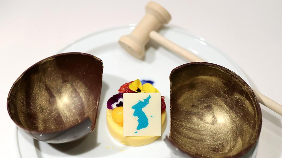 "A mango mousse cake decorated with a garnish in the shape of a unified Korean peninsula. The cake is in a wooden bowl, a symbol of Cold War confrontation, which will be broken by a hammer to symbolize the start of reconciliation. The South Koreans will serve Swiss chocolate, macaroons and cheesecake in a set of desserts that Seoul's presidential Blue House has named ""Memories of Swiss.""  (The Blue House / AFP)"