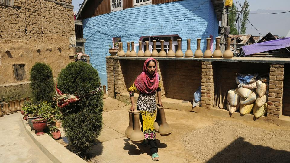 A woman carries freshly made tumbaknaris to a furnace where they will be baked. This Indian cousin to the Iranian dumbek, while not common elsewhere in India, is essential to Kashmiri folk music. Celebrations on any auspicious day are incomplete without 'chhakri' singing, and the tumbaknaris a mainstay in the instrument lineup. (Waseem Andrabi / HT Photo)