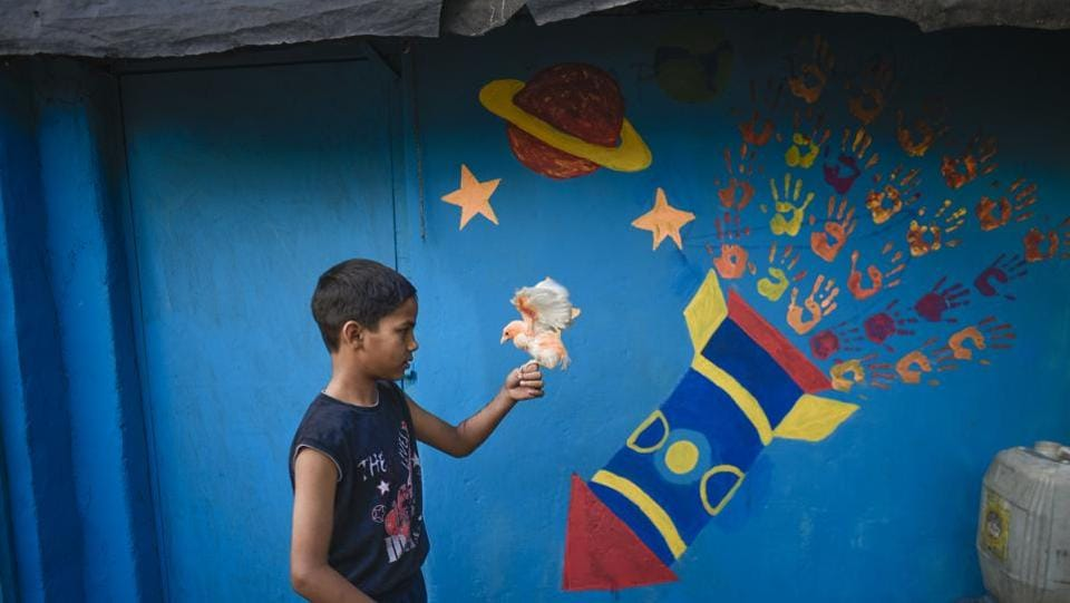 A boy plays with a chick in front of a newly painted wall of the slum. The NGO's focus is on developing social and emotional competencies within the community, and providing tools necessary for a cohesive, non-violent, and caring community that would ultimately equip them to lead happier and successful lives. (Burhaan Kinu / HT Photo)