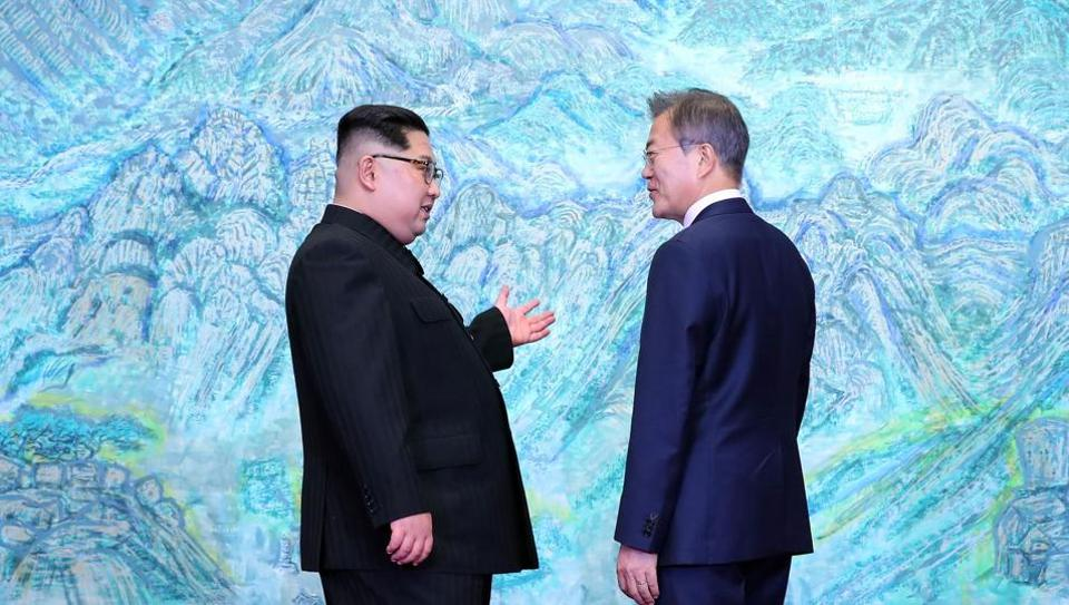 South Korea's President Moon Jae-in (R) speaks with North Korea's leader Kim Jong Un (R) during the Inter-Korean summit in the Peace House building on the southern side of the truce village of Panmunjom on April 27, 2018.