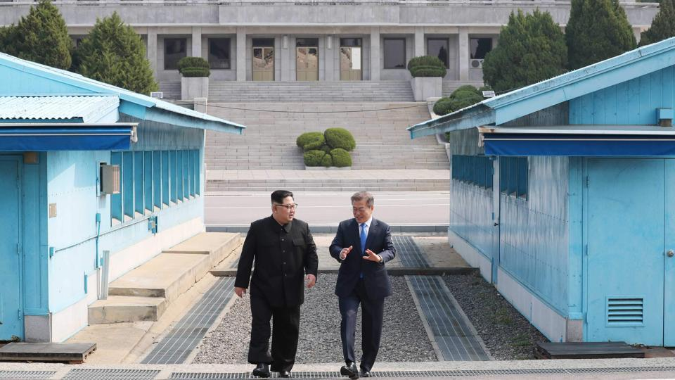 North Korea's leader Kim Jong Un (L) walks with South Korea's President Moon Jae-in (R) after crossing the Military Demarcation Line that divides their countries ahead of their summit at Panmunjom on April 27, 2018.