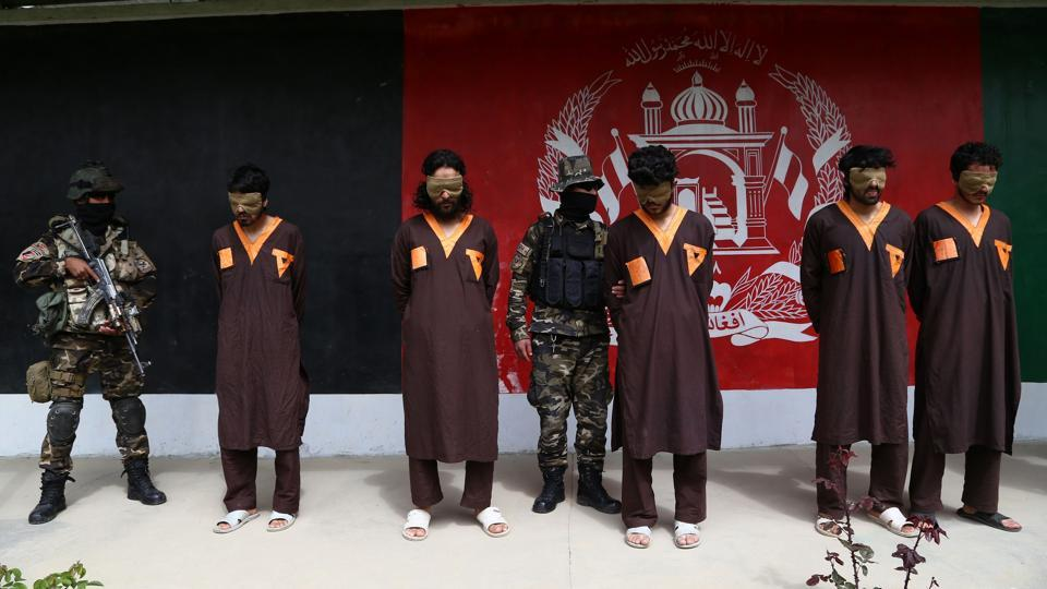 Afghan security forces stand next to arrested Taliban militants in Ghazni province on April 14, 2018.