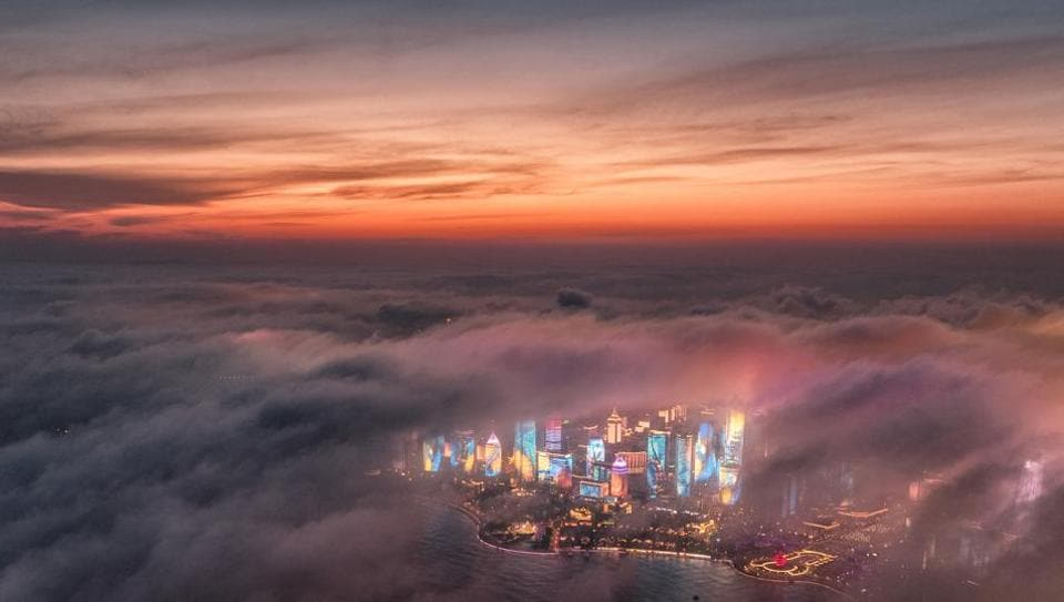 Advection fog drifts across skyscrapers on the waterfront in Qingdao in eastern China's Shandong Province. A weather system brought clouds and rain to parts of China on Saturday. (Lu Hui / Xinhua via AP)