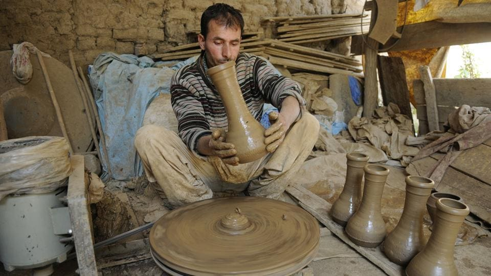 A potter works on an earthen tumbaknari, a goblet drum traditional to Jammu and Kashmir, at a workshop on the outskirts of Srinagar. This musical instrument has deep roots in the culture of Kashmir and is believed to have been brought to Kashmir by visitors and rulers who came in the olden days from Iran and the Middle East. (Waseem Andrabi / HT Photo)