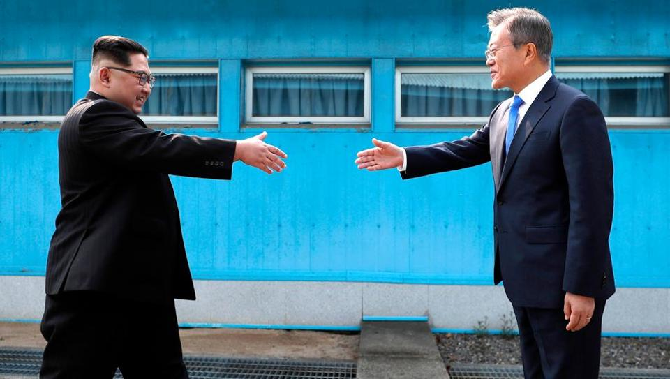 North Korean leader Kim Jong Un, left, prepares to shake hands with South Korean President Moon Jae-in over the military demarcation line at the border village of Panmunjom in Demilitarized Zone Friday, April 27, 2018.