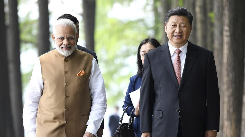 Prime Minister Narendra Modi (left) and Chinese President Xi Jinping walk together in Wuhan in central China's Hubei Province.