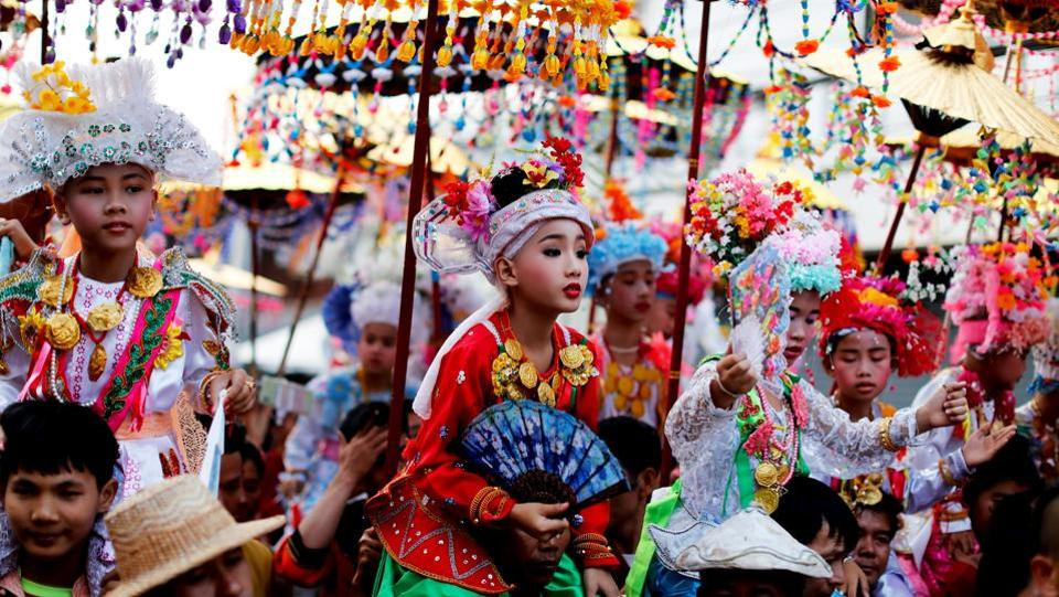 Golden umbrellas draped in beads and flowers provide shade for boys as young as seven riding on their fathers' shoulders in a procession through the mountain town of Mae Hong Son on Thailand's northern border. (Jorge Silva / REUTERS)