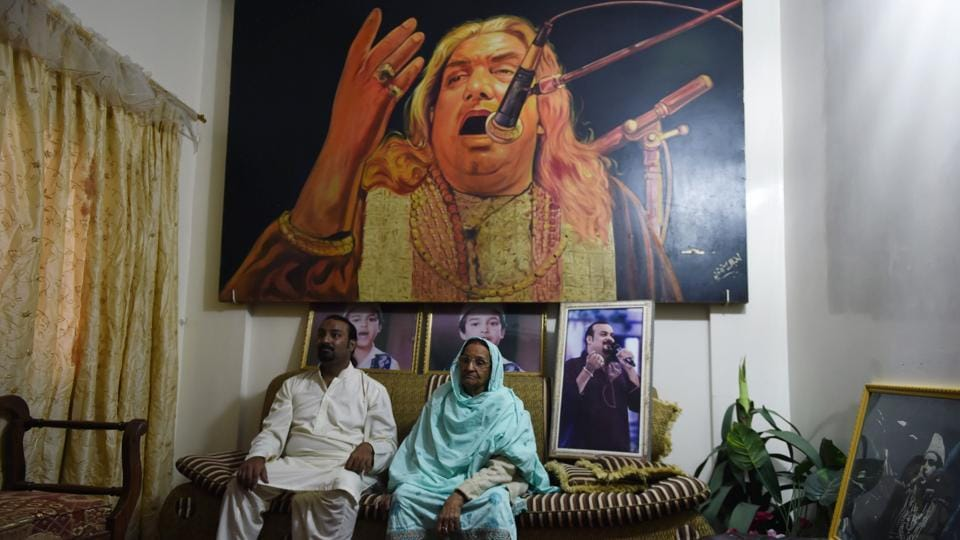 "Talha Sabri is flanked by his mother, an image of his father Qawwal Ghulam Farid Sabri overhead. ""Regardless of these threats, we have to keep on,"" he said. For Sabri's mother Asghari Begum however, the murder of her son marked a turning point for qawwali, ringing the death knell for its future. ""He has gone now,"" she said. ""And the passion of qawwali has gone with him."" (Rizwan Tabassum / AFP)"