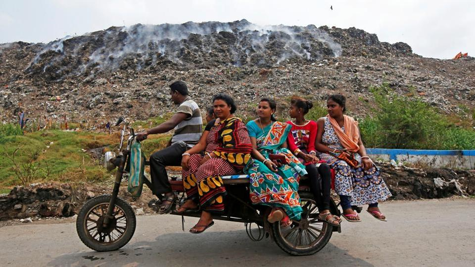 A man transports passengers on an improvised motor-rickshaw as they drive past a burning garbage dump site on the occasion of Earth Day, in Kolkata on April 22, 2018. (Rupak De Chowdhuri / REUTERS)