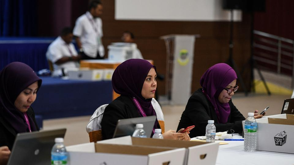 This picture taken on April 28, 2018 show members of the Election Commission of Malaysia (EC) playing with their phone before candidates handing over election documents during the nomination day ahead of the country's 14th general election in Pekan.