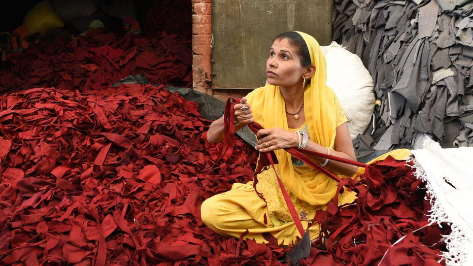 A woman shreds clothes with special slicers. The shredded woollen scrap is turned back into a yarn called shoddy. The piles of clothes have already been sorted into the basic colour families of gray, red, blue, camel and green --winter clothing colours in the West. Shoddy blankets are rough, coarse and usually brown or grey but the Chinese blankets are light, soft and come in a variety of colours. (Vipin Kumar / HT Photo)