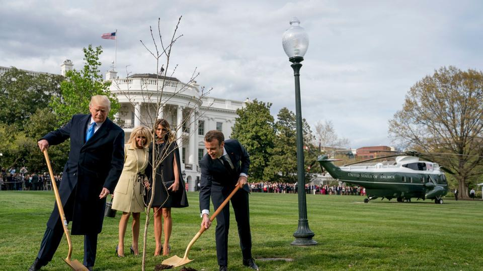First lady Melania Trump, second from right, and Brigitte Macron, second from left, watch as President Donald Trump and French President Emmanuel Macron participate in a tree planting ceremony on the South Lawn of the White House in Washington.