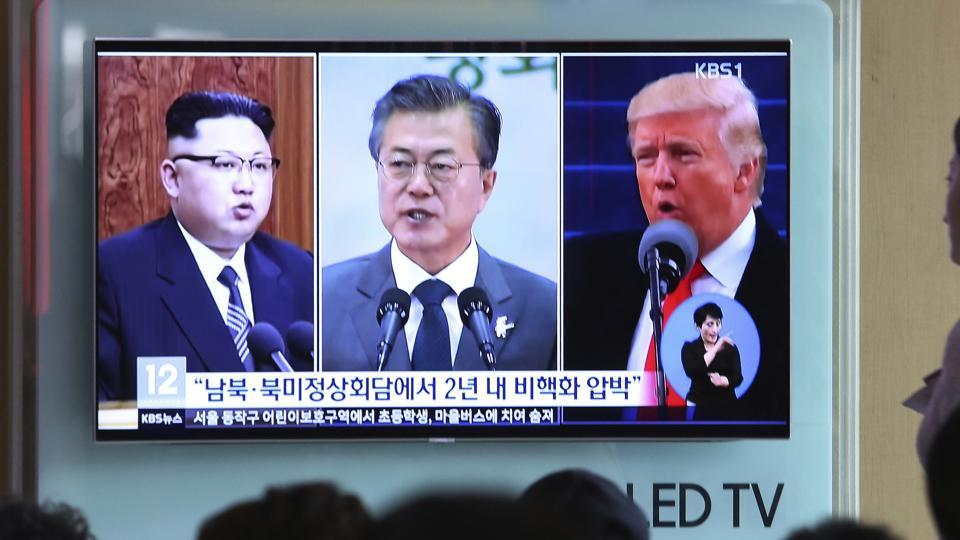 People watch a TV screen showing file footage of US President Donald Trump, right, South Korean President Moon Jae-in and North Korean leader Kim Jong Un, left, during a news program at the Seoul Railway Station in Seoul, South Korea, Wednesday, April 18, 2018.
