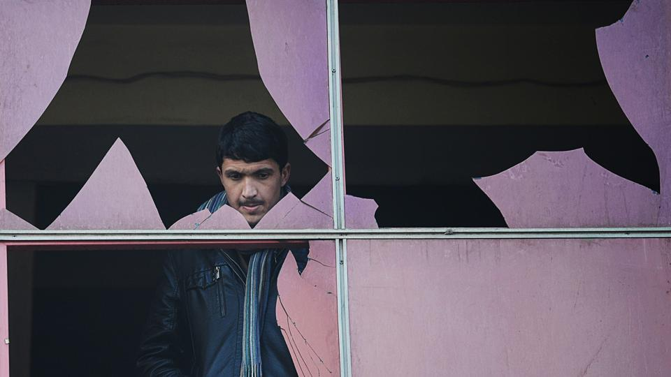 An Afghan resident looks through a broken window at the site of a suicide attack in Kabul on January 26, 2014. Marai often spoke candidly of sleepless nights haunted by what he had seen and endured, and of his fears as Kabul slipped further into violence. (Shah Marai / AFP File)