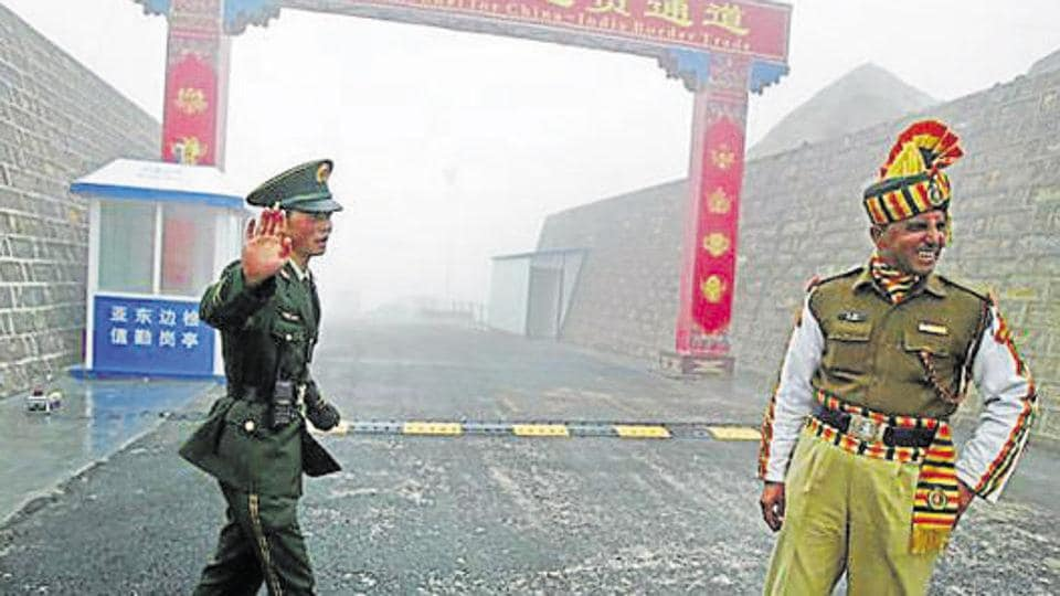 This file photo taken on July 10, 2008 shows a Chinese soldier (L) next to an Indian soldier at the Nathu La border crossing between India and China in Sikkim.