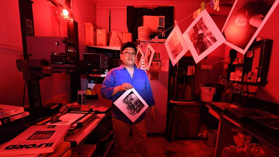 Vicky Luthra, an expert photograph developer and printer, poses with a black and white print in the darkroom at his SV Photographic printing studios in New Delhi, India. In times of digital cameras and platforms to publish images instantly, Luthra caters to photographers still patient enough to wait for a an image's journey from film to photographic print before the final reveal. (Prakash Singh / AFP)