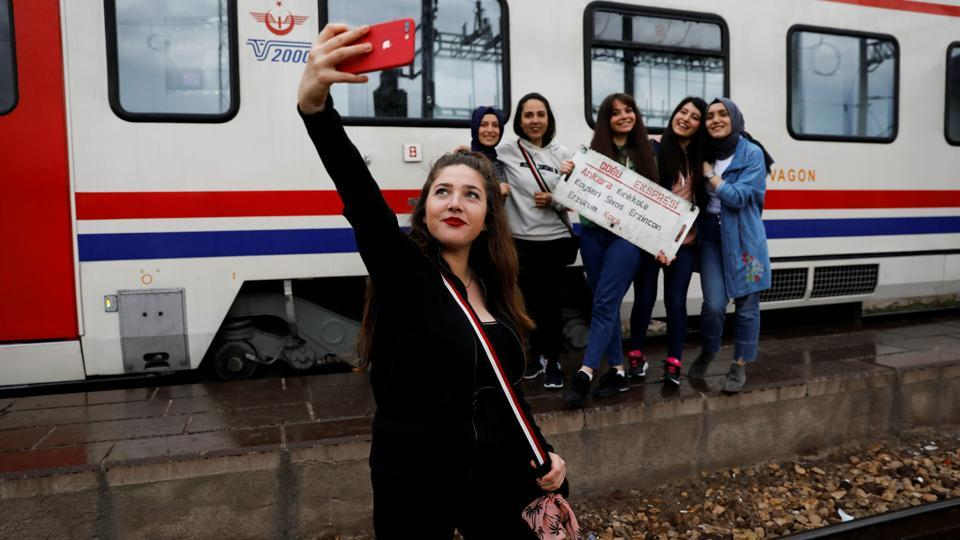 As the references on social media to the train journey proliferated, must-do rituals emerged for all travellers. It's now customary to take snaps holding the signs in the carriages showing the route. (Umit Bektas / REUTERS)