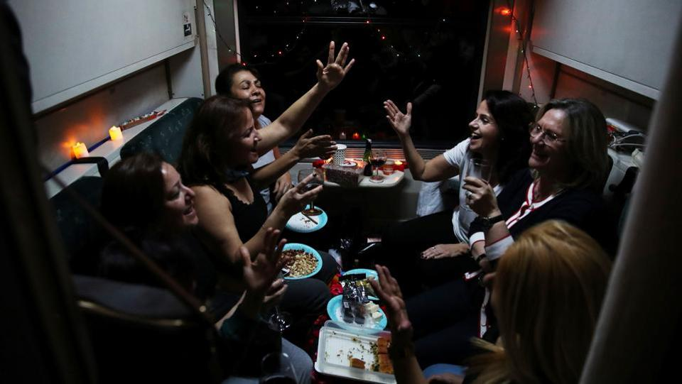 Passengers listen to music on board the Eastern Express travelling through Sivas province. Tourists decorate compartment with Christmas lights, candles and balloons, holding big parties in spaces designed for four only, taking group photos. (Umit Bektas / REUTERS)