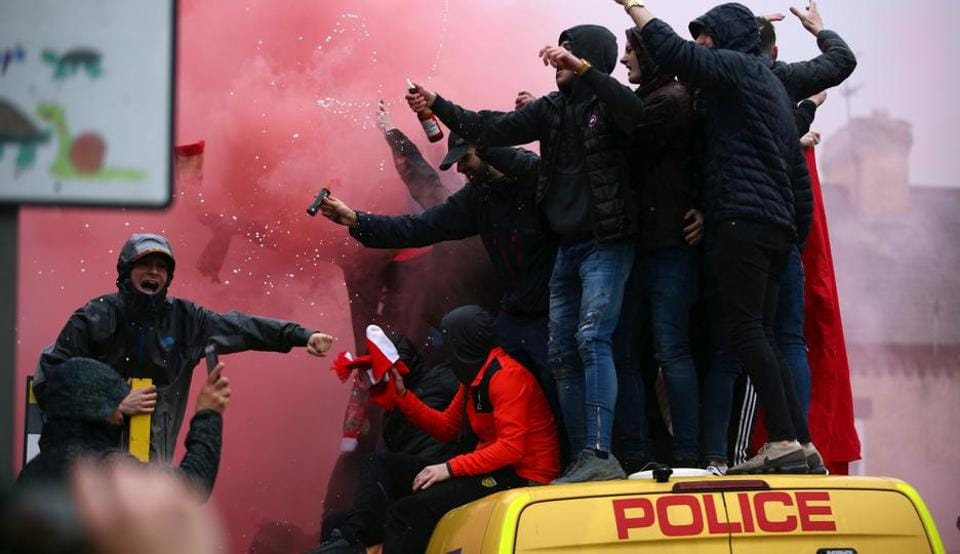 In this April 24, 2018 file photo, football fans stand on top of a police van amid smoke from flares outside the stadium before the UEFAChampions League semi-final first leg match between Liverpool FC and AS Roma at Anfield. Off-pitch tensions are high ahead of the second leg in Rome as Liverpool supporter Sean Cox lies in a coma after being attacked before last week's match. Two Roma supporters were arrested on suspicion of attempted murder.