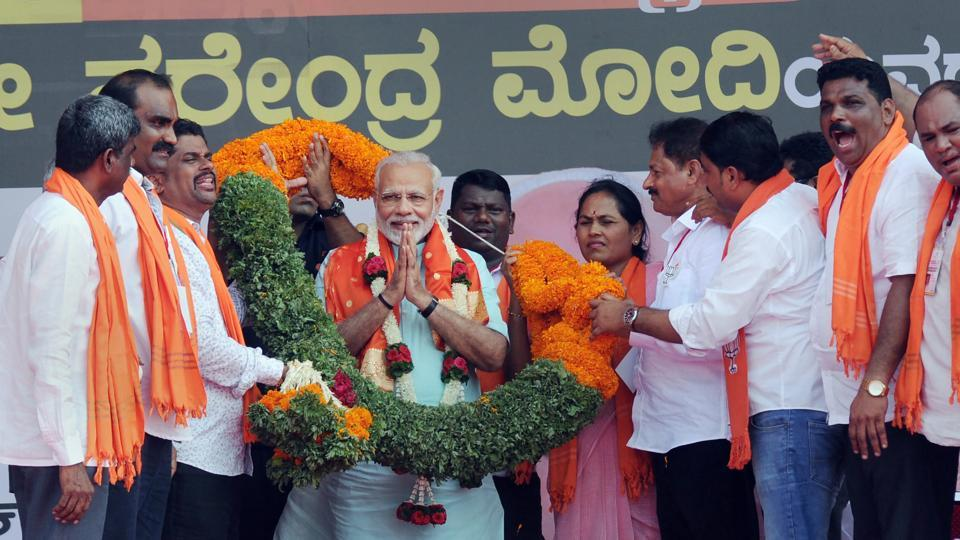 Prime Minister Narendra Modi being garlanded by BJP workers at an election campaign rally ahead of the Karnataka polls, in Udupi on Tuesday.