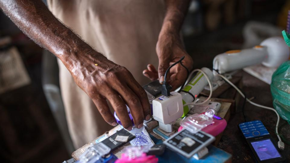 A vendor plugs a smartphone battery into a solar powered charging unit at a grocery store in Sujawal. It's been a sound investment so far. Dino now makes as much as 3,000 rupees extra each month from customers attracted by the perks. He'd spend more earlier to run a gasoline generator. (Asim Hafeez / Bloomberg)