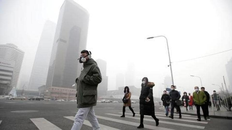 A man wearing a respiratory protection mask walks toward an office building during the smog after a red alert was issued for heavy air pollution in Beijing's central business district, China.