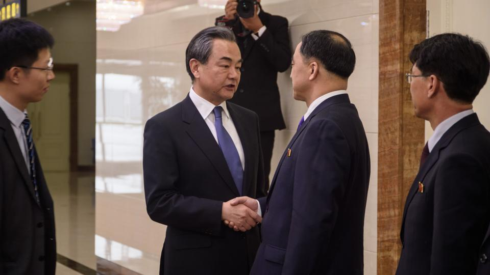 China's foreign minister Wang Yi (centre L) shakes hands with North Korea's vice foreign minister Ri Kil Song (centre R) after arriving at Pyongyang international airport on May 2, 2018.