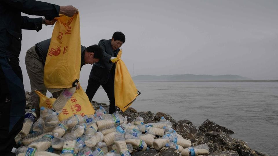 Activists empty bags of bottles on Ganghwa island. According to a survey conducted in 2015, 81% of North Korean defectors had watched foreign films on USB sticks before they fled the country. Thae Yong Ho, North's former deputy ambassador to Britain who defected to the South in 2016, once said that disseminating outside information was a way to educate North Koreans to resist the authorities. (Ed Jones / AFP)
