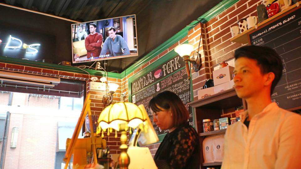 """Staff members stand behind a counter as a television plays the US sitcom Friends at the """"Central Perk"""" coffee shop in Shanghai. Millions of Chinese Friends fans are heartbroken after a video site pulled the show, beloved by millennials in China for its endearing young characters and as an English conversation resource. (AFP)"""