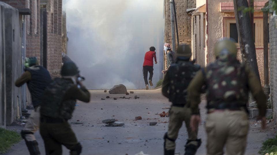 A protester runs for cover amid tear gas smoke as a policemen (left) fires pellet guns during a protest in Srinagar.