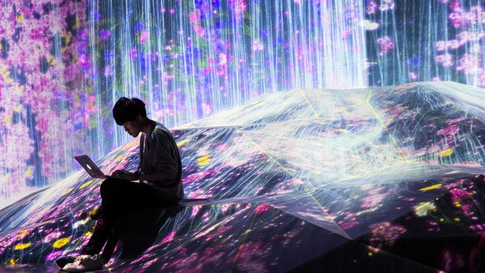 The waterfall appears to run down the wall of a room and across the floor, but the flow is an illusion -- a digital exhibit at a new interactive museum in Tokyo.