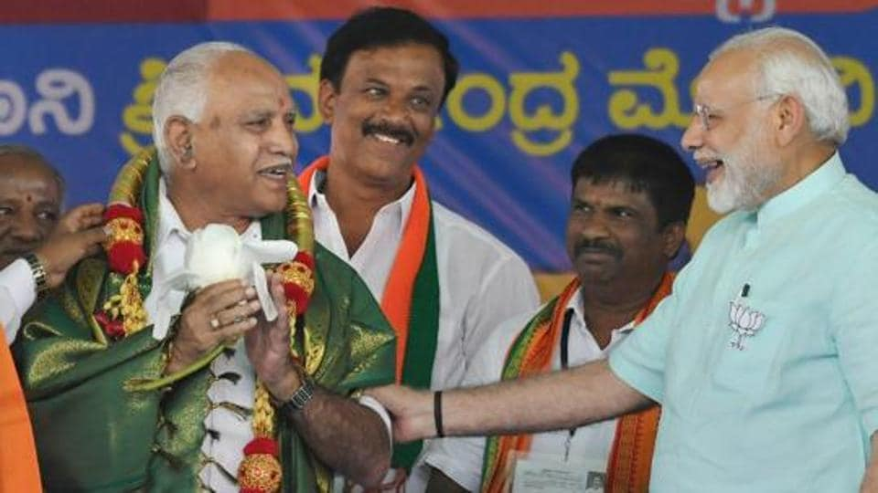 Prime Minister Narendra Modi and BJP's chief ministerial candidate BS Yeddyurappa share a lighter moment during Karnataka election campaign rally at Chamarajanagar on Tuesday.