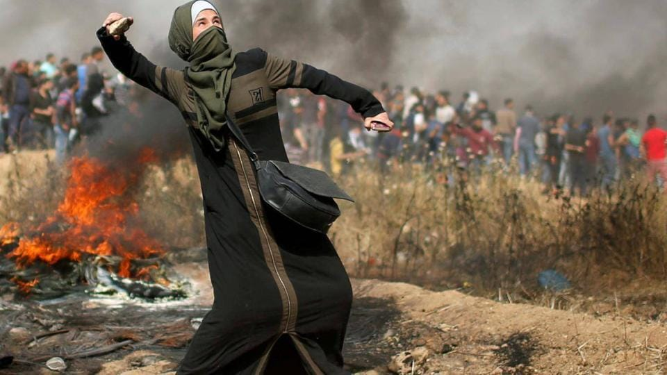 A girl hurls stones during clashes with Israeli troops at a protest where Palestinians demand the right to return to their homeland, at the Israel-Gaza border.