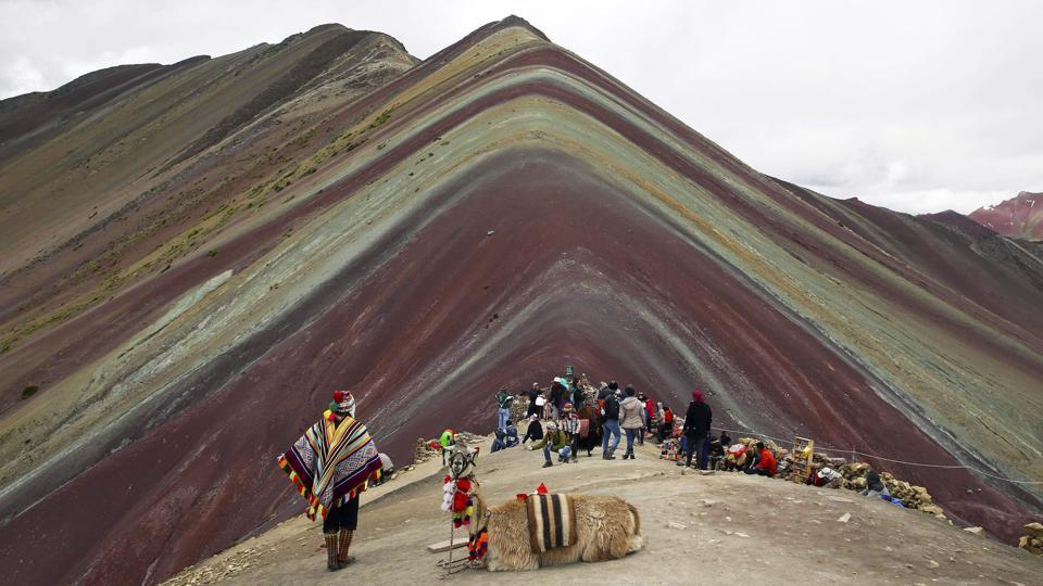"An Andean man and his IIama rest on mountain formed of stripes of turquoise, lavender and gold known as ""Rainbow Mountain."" This ridge of multicoloured sediments laid down millions of years ago was pushed up as tectonic plates clashed. Just five years into its discovery by the outside world, Rainbow Mountain has earned a must-see status on Peru's burgeoning backpacker circuit. (Martin Mejia / AP)"