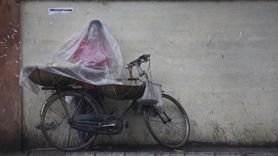 A fruit vendor stands covered in plastic to protect himself from rain in Guwahati, Assam on May 2, 2018. (Anupam Nath / AP)