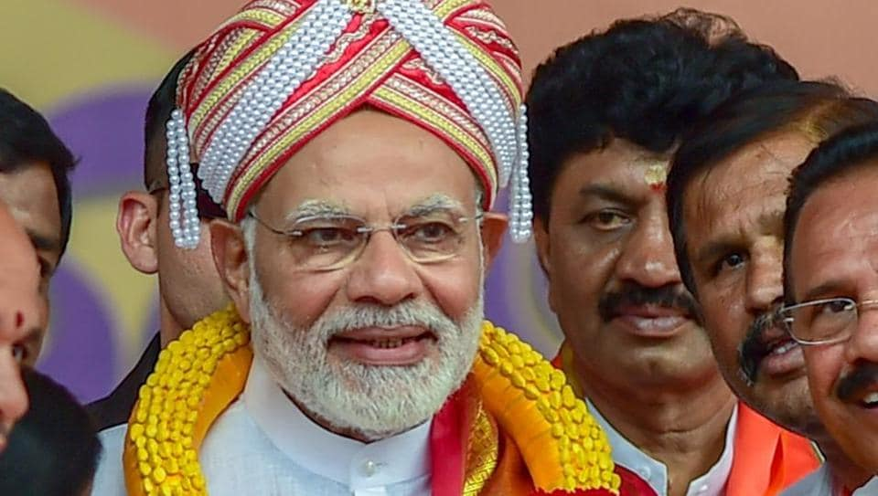 Prime Minister Narendra Modi being presented a Mysore peta and memento by BJP workers during a public rally for the Karnataka assembly elections, in Bengaluru on Thursday.