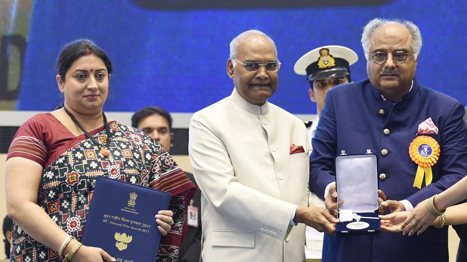 I&Bminister Smriti Irani flanks President Ram Nath Kovind as he gives Boney Kapoor the Best Actress award given posthumously to his wife Sri Devi for her Hindi movie Mom during the 65th National Film Awards on May 3, 2018.