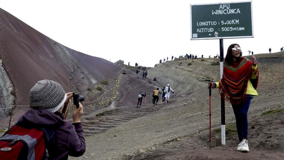 A tourist poses for a photograph at the entrance that leads to Rainbow Mountain. Visitors must climb for two hours to reach the peak in the Peruvian Andes which stands 16,404 feet above sea level. This tiresome trek turns worthy when the magical beauty of Rainbow Mountain unfurls before the eyes. (Martin Mejia / AP)